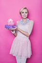 Beautiful blonde woman with cream colored dress holding pink and purple gift boxes studio portrait over bright background Stock Photography