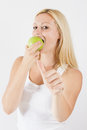 Beautiful blonde woman eating green apple portrait of Royalty Free Stock Image
