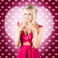 Beautiful blonde woman gesturing heart shape pretty girlfriend heartfelt feeling of romance with hands pink hearts background Stock Photos