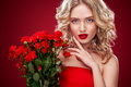 Beautiful blonde woman holding bouquet of red roses. Saint Valentine and International Women`s Day, Eight March Royalty Free Stock Photo