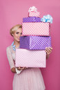 Beautiful blonde woman looking through colorful gift boxes. Soft colors. Christmas, birthday, Valentine day, present Royalty Free Stock Photo