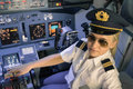 Beautiful blonde woman pilot wearing uniform at flight simulator and hat with golden wings modern aircraft cockpit ready for take Royalty Free Stock Photography
