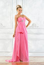 Beautiful blonde woman in a pink long dress. Royalty Free Stock Photo