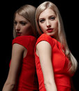 Beautiful blonde woman portrait of young long haired in red dress at mirror Royalty Free Stock Images