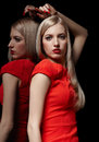 Beautiful blonde woman portrait of young long haired in red dress posing at mirror Stock Photography