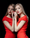 Beautiful blonde woman portrait of young long haired in red dress touching her reflection in mirror with manicured fingers Stock Photos