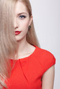 Beautiful blonde woman portrait of young in red dress with half of face behind long hair Royalty Free Stock Photos