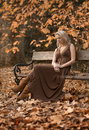 Beautiful blonde woman sits in autumn park in brown dress young on outdoor bench Royalty Free Stock Images