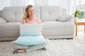 Beautiful blonde woman sitting on the floor using laptop Royalty Free Stock Photo
