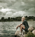 Beautiful Blonde Woman Sitting near the Water Stock Images