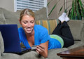Beautiful blonde woman using laptop on couch Royalty Free Stock Image