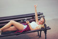Beautiful blonde woman using phone lying on a bench in the Royalty Free Stock Photo