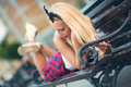 Beautiful blonde woman using phone lying  on a bench Royalty Free Stock Photo