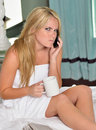 Beautiful blonde woman in white towel with coffee and phone stunning sexy young wearing only bath sitting on bed holding cup while Royalty Free Stock Image