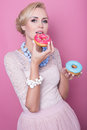 Beautiful blonde women taste colorful dessert fashion shot soft colors woman studio portrait over pink background Royalty Free Stock Photography