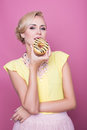 Beautiful blonde women with yellow blouse taste yellow dessert. Fashion shot. Soft colors Royalty Free Stock Photo