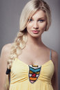 Beautiful blonde young woman braid hairdo yellow dress looking camera Royalty Free Stock Image