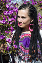 Beautiful blue eyed woman with the african pigtails among branches of flowering magnolia Stock Photo