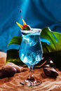 Beautiful blue lagoon cocktail with ice in a still life on the sand Royalty Free Stock Photo