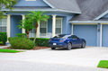 Beautiful blue luxury house home with blue sports car a big lush green grass and palm trees in the front yard a in the driveway Royalty Free Stock Photos