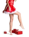 Beautiful body of christmas girl and long slim perfect barefoot legs in red dress near many red gift boxes isolated on Stock Photography