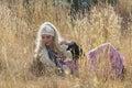 Beautiful bohemian blonde woman lying in field of grass