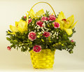 Beautiful bouquet of bright flowers in basket on light background Royalty Free Stock Photos