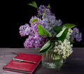 A beautiful bouquet of lilac in a vase on a black background