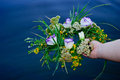 Beautiful bouquet of a wreath of wildflowers a girl holding a river over water Royalty Free Stock Photo