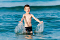 Beautiful boy making splashes in the middle of sea waves Royalty Free Stock Photo