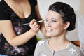 Beautiful bride applying wedding make-up by make-up artist Royalty Free Stock Images