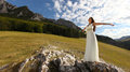 Beautiful bride with arms up in nature panorama of young woman long white dress stretching mountains background Royalty Free Stock Photography