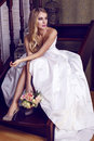 Beautiful bride with blond hair in elegant wedding dress with bouquet fashion interior photo of holding a of flowers sitting on Stock Photo
