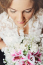 Beautiful bride close up of a looking down at her bouquet focus on eyelashes Stock Photos