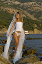 image photo : Beautiful bride in a corset is on the rock