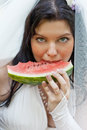 Beautiful bride eats a  water-melon Royalty Free Stock Photo