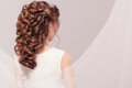 Beautiful bride with fashion wedding hairstyle - on gray background. Closeup portrait of young gorgeous bride. Wedding