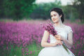 Beautiful bride in a flower field. The girl in a white dress with a bouquet in a summer field at sunset Royalty Free Stock Photo