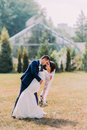 Beautiful bride with gorgeous white wedding dress and groom in stylish blue suit posing outdoor on lawn. Greenhouse at Royalty Free Stock Photo