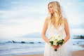 Beautiful bride gorgeous woman on tropical beach at sunset with flower bouquet Stock Photos