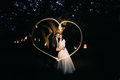 Beautiful bride and groom in evening park holding each other under tree decorated with many lanterns. Lightpainted heart Royalty Free Stock Photo