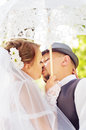 Beautiful bride and groom kissing under an umbrella on the nature Royalty Free Stock Image