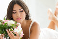 Beautiful bride holding nuptial bouquet in white lingerie Stock Photography
