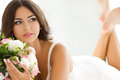 Beautiful bride holding nuptial bouquet in white lingerie Royalty Free Stock Photography