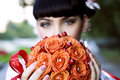 Beautiful bride holding orange flowers a bouquet of roses Stock Photos