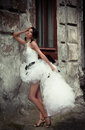 Beautiful bride leaning against the wall of an old building Stock Photos