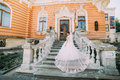Beautiful bride in magnificent dress with long tail going up the stone stairs to romantic vintage building