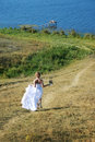 Beautiful bride runs to the river Royalty Free Stock Photography