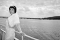 Beautiful bride on a ship in river retro style black and white image of marvelous landscape behind her Royalty Free Stock Images