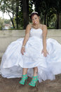 Beautiful bride shows her new shoes a lovely young seated outdoors proudly displays Stock Photography